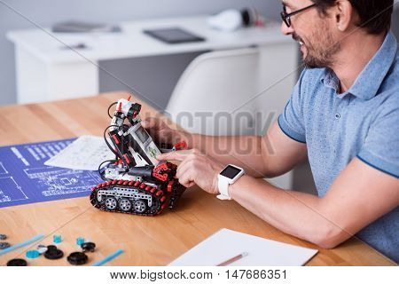 Contemporary advancements. Cheerful delighted senior man sitting at the table and using robot while testing it