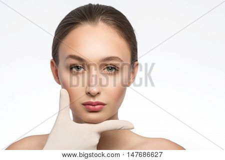 Beautiful girl has perfect face proportion. She is standing and looking at camera confidently. Female fingers are touching her chin. Isolated