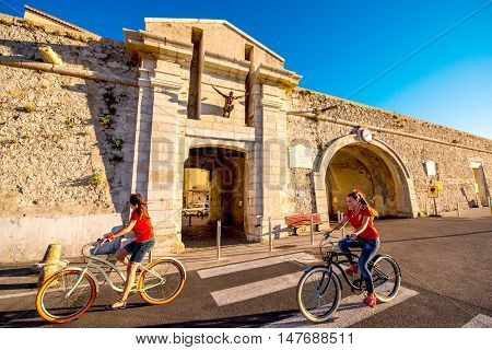 Antibes, France - June 14, 2016: Ancient city wall with gates and women ride a bicycles near Vieux harbor in Antibes village in France.