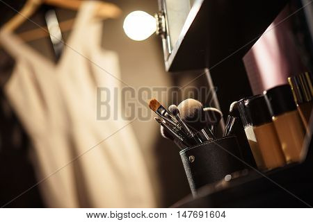 Close up of make-up brushes and foundation near mirror backstage. Elegant dress hanging on background