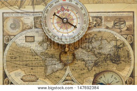 Old vintage retro golden compass on ancient map.