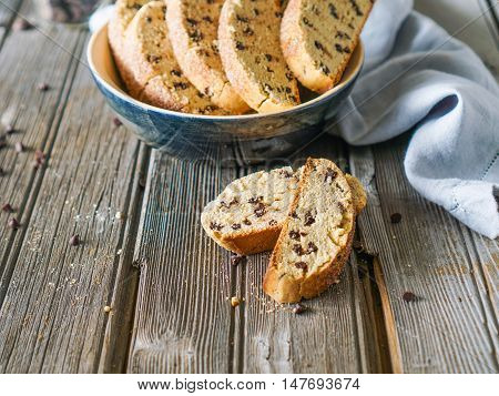 Delicious biscotti or cantuccini with chocolate chips on wooden vintage table, traditional Italian biscuit or cookies. Selective focus, toning.