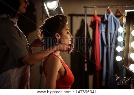 Backstage preparation. Skillful young beautician is applying powder on female face. Young model is sitting and looking at mirror with satisfaction