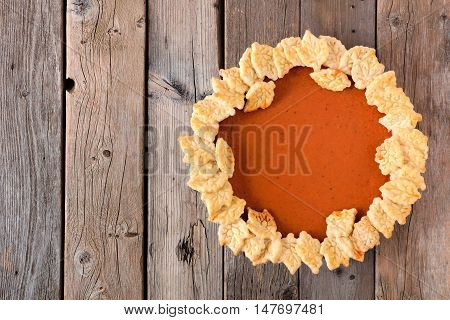 Thanksgiving Pumpkin Pie With Autumn Leaf Pastry Design, Above View On A Rustic Wood Background