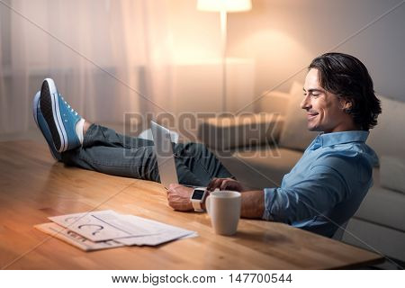 Easy work . Handsome relaxed young man putting his lags on the table and smiling while using laptop.