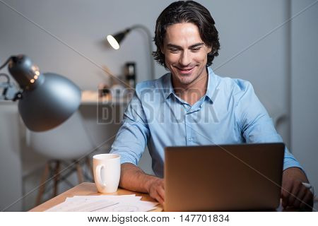 Dream work. Handsome positive young man sitting at the table and putting his lags on the table while using tablet.