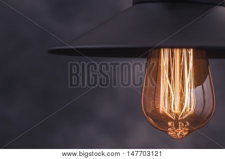 Retro light lamp with Edison light bulb from right border of dark blurred background. Closeup. Toned