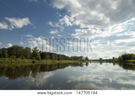 river with blue sky and white clouds Bug river in Poland