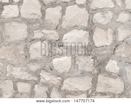 exterior decorative light gray old rough wall made of natural sandstone with potholes and streaks in country style