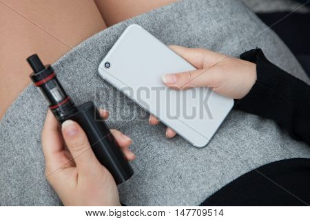 Girl Holding Vaporizer And Modern Smart Phone