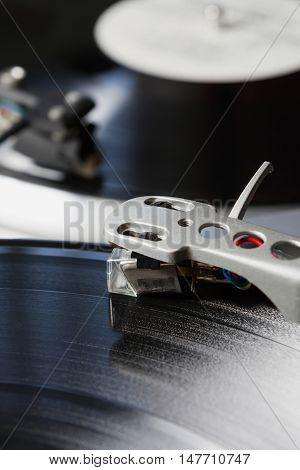 DJ turntable needle playing vinyl recod with music.