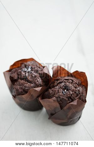 Two Tasty Chocolate Muffins On Wooden Table