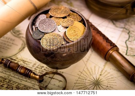 Treasure pot with coins on old map background