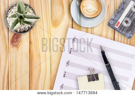 music paper,cactus, fountain pen, tape cassette and coffee latte on wooden table