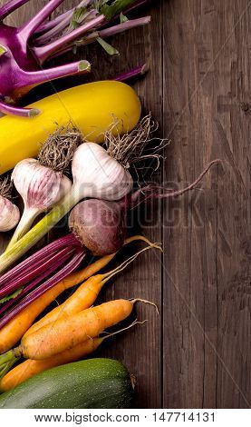 Various vegetables on dark wooden background. Zucchini eggplant squash and beets
