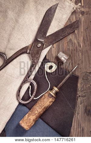 Vintage scissors, awl and thimble with leather and cloth on old wooden background