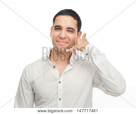 happy smiling young man showing a call me sign isolated against white studio background