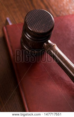 Wooden gavel on maroon book on table