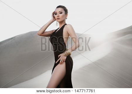 Professional photo shoot in desert. Beautiful sexy asian woman model in desert