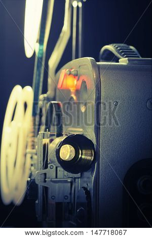 Old amateur super-8 film movie projector in dark. Toned