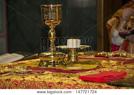 Holy Eucharist in orthodox Church: Consecrated bread and wine in chalice on Holy See during orthodox liturgy on Easter 2016 year. Trinity Cathedral in Donetsk, Ukraine.
