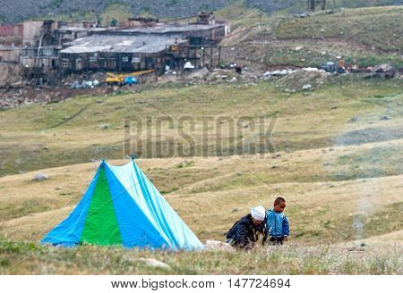 ALTAY, RUSSIA - JULY 24, 2007: Altay woman who came to the Dzhumalinsky thermal spring cooks dinner near his tent in Altay mountains Russia. Dzhumalinsky Thermal Spring contains radon
