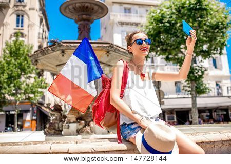 Young female traveler making selfie photo with french flag near the fountain on place de Gaulle in the center of Cannes city in France