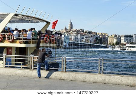 Istanbul Turkey - January 1 2011: Passengers on the Eminonu pier engine. Galata bridge and Galata tower is seen in the background