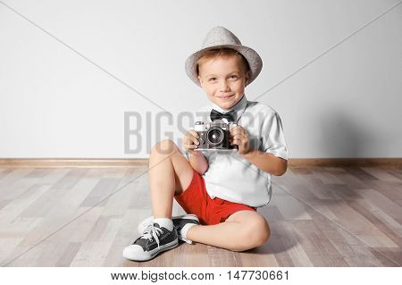 Little boy with vintage camera on floor in empty room