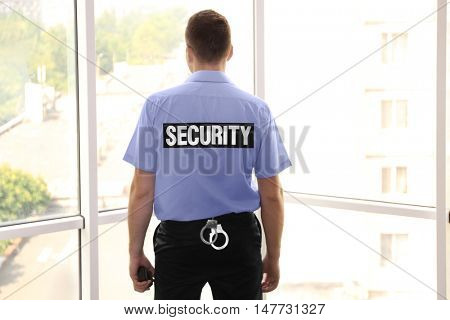 Security man standing back on window background