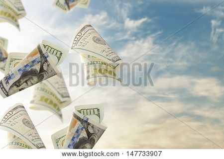 Flying bonds Of One Hundred Dollar Bills against blue sky background. Abstract money backdrop