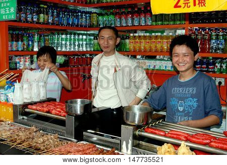 Chengdu China - September 20 2006: Chinese family in their food shop on Qing Nian Lu selling sodas and a variety of grilled meats and sausages