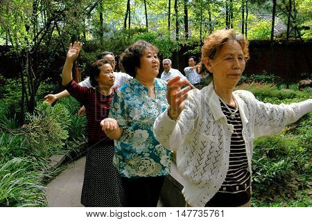 Chengdu China - May 8 2008: Senior citizens participating in group exercises in the gardens of the Manjursi Monastery at the Wen Shu Temple