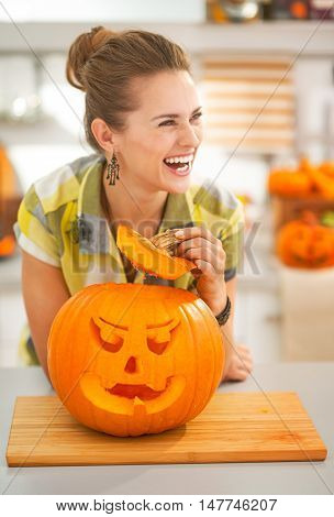 Housewife In Kitchen With A Big Orange Pumpkin Jack-o-lantern