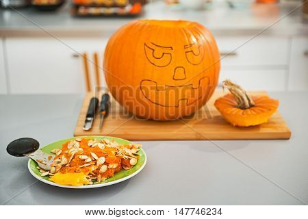 Frightful Treats on the way. Closeup on pumpkin seeds on the plate in the Halloween decorated kitchen with big pumpkin Jack-O-Lantern in background