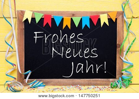 Chalkboard With German Text Frohes Neues Jahr Means Happy New Year. Party Decoration Like Streamer, Confetti And Bunting Flags. Yellow Wooden Background With Vintage, Retro Or Rustic Syle