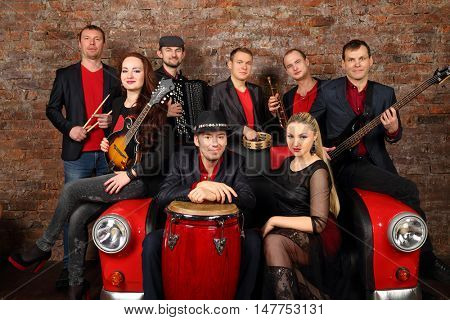 Brass band of eight people in red and black clothes pose in studio with car couch