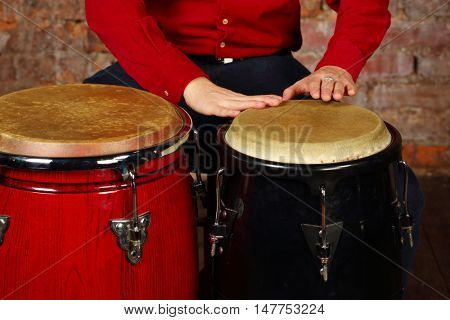 Hands of young man hit modern drums in studio with red brick wall