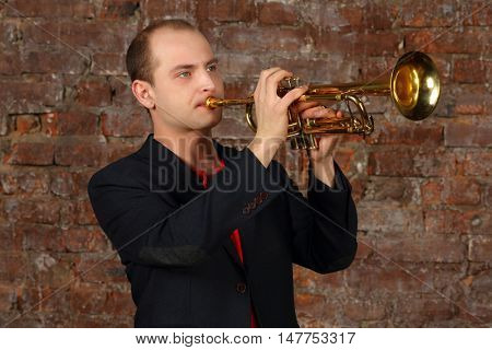 Young handsome man in suit plays trumpet in studio with brick wall
