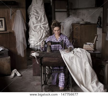 Beautiful young bride wearing flannelette pyjamas makes last minute adjustments to her Wedding Dress at an ancient old treadle sewing machine