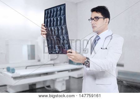 Portrait of a male radiologist looking at x-ray or roentgen image in the hospital room