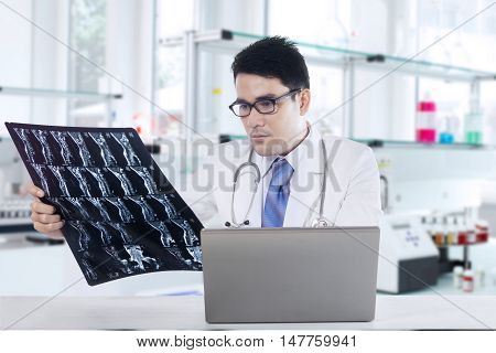 Picture of a male physician looking at x-ray or roentgen image with laptop on the table shot in the laboratory