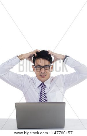 Portrait of a stressful male entrepreneur scratching his head with notebook computer on the table