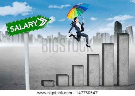 Growing salary concept. Young businesswoman jumping above growing graph with umbrella and salary text