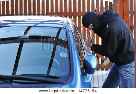 Young man in mask trying to steal a car