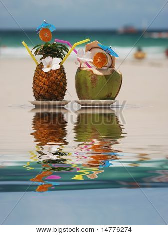 Tropical cocktails on the beach. Reflection in water.