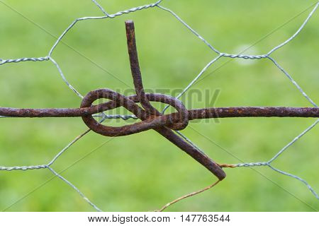 Abstract: Fence wire pretzels made by the twisted wire knots made in the rural fence. Taken at the Edan Valley Lookout South Australia. Shallow depth of field and focus.