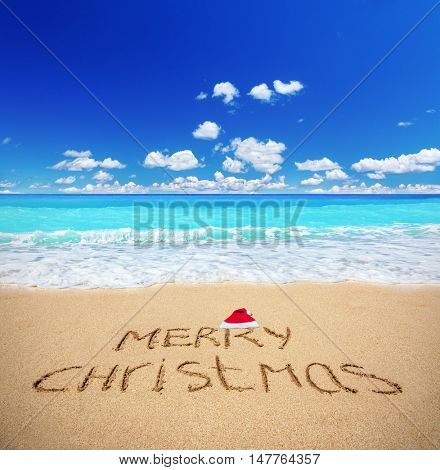 Merry Christmas written on a sandy beach