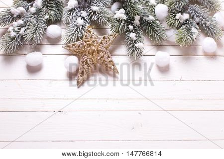 Christmas star and branches fur tree on white wooden background. Decorative christmas composition. Selective focus. Place for text.