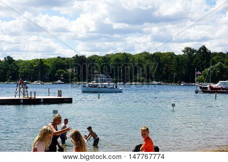 HARBOR SPRINGS, MICHIGAN / UNITED STATES - AUGUST 1, 2016: People enjoy swimming, playing, and sunbathing at the Zorn Park Public Beach near downtown Harbor Springs.